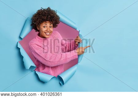 Cheerful Young Curly African American Woman Recommends Something Points At Blank Space Demonstrates