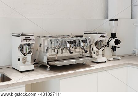 Traditional professional Italian espresso machine and coffee grinders in the new kitchen