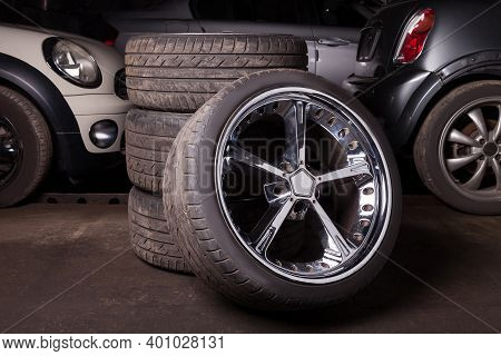 Automobile Composition Made Up Stack Of Tires And Wheel With Shiny Metal Disc In The Foreground Agai
