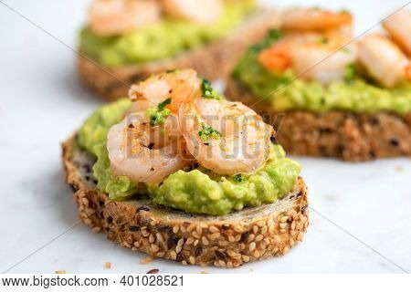Healthy Appetizer Or Snack Avocado Shrimp Bruschetta With Whole Grain Bread On White Marble, Closeup