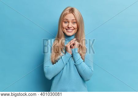 Pretty Blonde Woman With Toothy Smile Keeps Hands Together Feels Glad To Hear Heartwarming Words Or