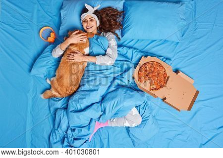 Pleased Young Woman Plays With Her Favorite Dog Embraces Pet Spend Free Time In Bed Surrounded With