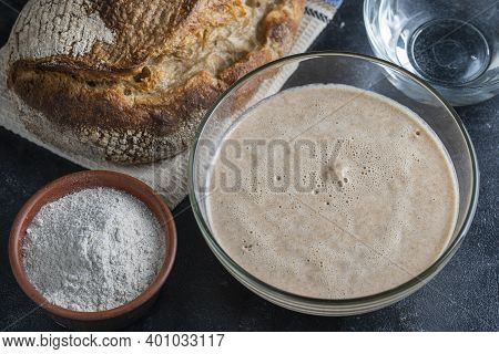 Yeast-free Sourdough Bread, Flour, Water And Glass Jar With Dough Leaven On The Table. Preparing Yea
