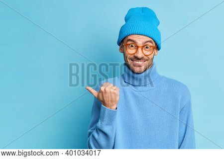 Horizontal Shot Of Cheerful Guy With Bristle Points Thumb On Left Side Wears Blue Hat And Turtleneck