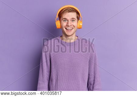 Handsome Teenage Boy Smiles Gladfully Wears Jumper Stereo Headphones Listens Pleasant Melody Isolate