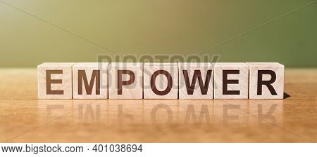 Empower Is Word Written On Wooden Blocks On A Wooden Table. Concept For Your Design.