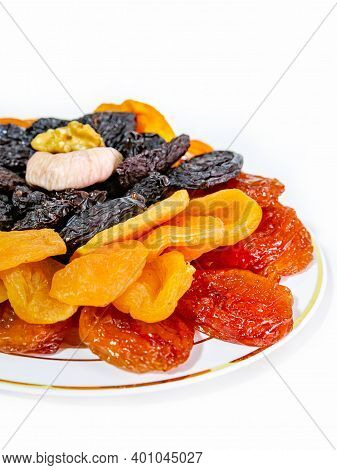 A Set Of Dried Fruits On A Plate. Dried Apricots, Prunes, Figs. Isolate. Close Up