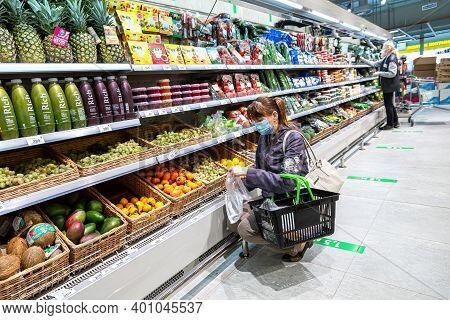 Samara, Russia - October 8, 2020: Young Woman Choosing Fresh Grapes At Shopping In Supermarket