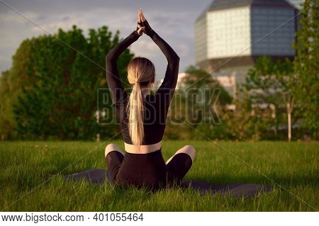 Woman Meditating Relaxing In Lotos Yoga Pose In Earphones And Listening Music. Girl Doing Yoga Sitti