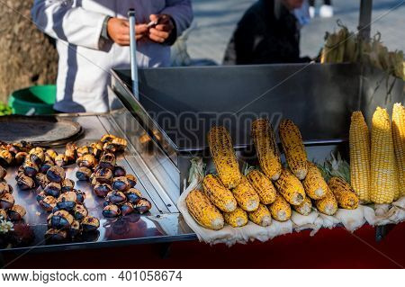Chestnuts And Corn Roasting, Blacked And Bursting Open, From A Street Vendor In Autumn.