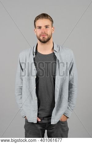 Man Bearded Strict Face Wears Casual Clothes, Grey Background. Man With Beard Unshaven Guy Looks Han