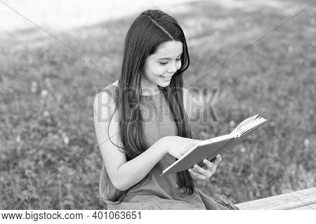 Read And Look What Great Things Are In Book. Happy Girl Read Book On Park Bench. Small Reader On Sum