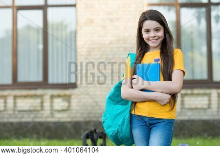 Happy Kid With Long Hair In Casual Style Hold School Bag And Book For Reading, Copy Space.