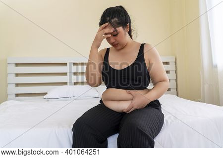 Obesity Unhealthy Concept. Overweight Woman Wear Sport Bar Pinches Fat On Her Belly Large Size While