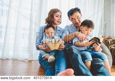 Two Parents Are Teaching Their Sons To Read In Living Room At Home. People Lifestyle And Education L