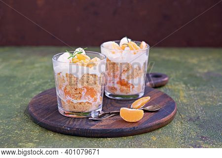 Layered Dessert In A Glass Of Shortbread, Fresh Mandarin And Whipped Cream Or Yoghurt On A Brown Woo