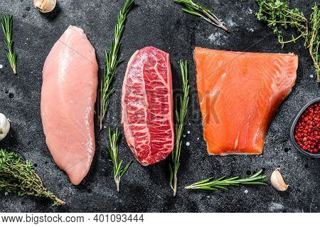 Different Types Of Raw Meat With Herbs. Beef Top Blade, Salmon Fillet And Turkey Breast. Steaks. Bla