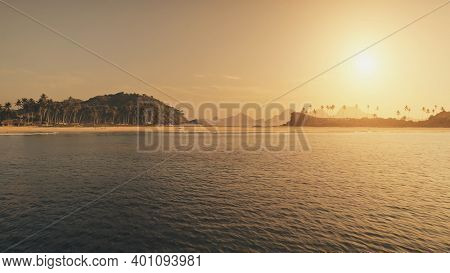 Sunset seascape at sand beach aerial. Summer tourist vacation at tropic paradise island with palm trees at sea shore. Nobody nature landscape of El Nido Islet, Philippines. Cinematic drone shot