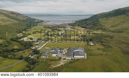 Scottish whisky distillery at village aerial. Road, cottages, houses at green mountain valley. Summer cloudy day. Nobody nature landscape of Arran Island, Scotland. Cinematic drone shot