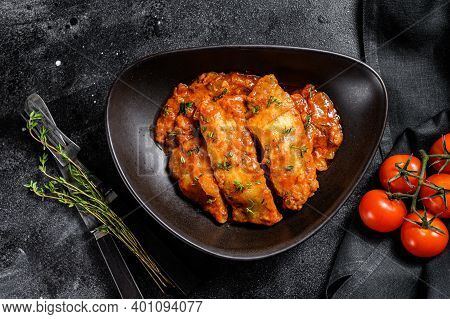 Baked Halibut Fish With Tomato Sauce. Black Background. Top View