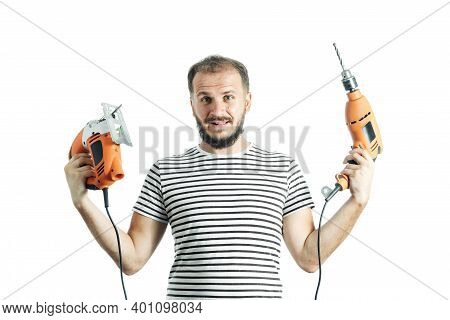 Portrait Of Stupid Handyman Holding Orange Drill And Electric Jigsaw Isolated On White