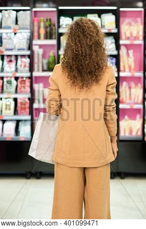 Back view of young elegant brunette female customer with paperbag standing in front of large display with various beauty products