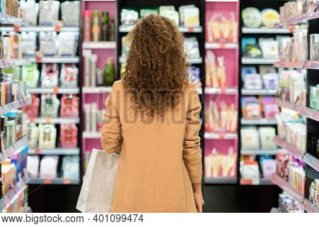 Back view of young brunette curly female customer with paperbag standing among large displays with various beauty products