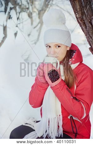 Girl drinking hot tea under a tree
