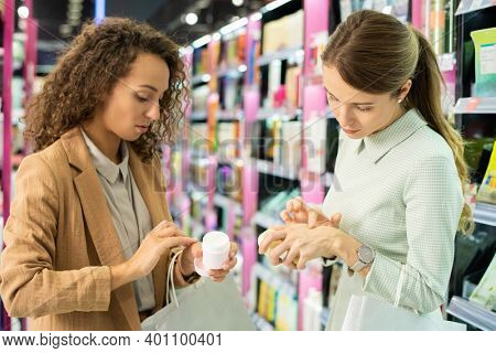 Two young elegant female customers with paperbags applying cosmetic cream on their hands while testing it and choosing which to buy