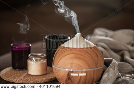 Oil Diffuser On Blurred Background Near Candles. Aromatherapy And Health Care Concept.