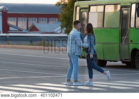 Guy Escorts Girl To Bus, Hugs And Kisses. Couple In Love Saying Goodbye At The Bus Stop.