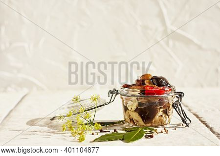 Marinated Mushrooms In Glass Jar, Herbs And On Clear Background. Canned Vegetatian Dish. Natural Lig
