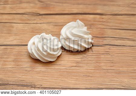 Two White Meringues On A Wooden Table