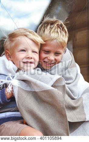 Two Brothers Hug And Have Fun Together Under A Warm Plaid.