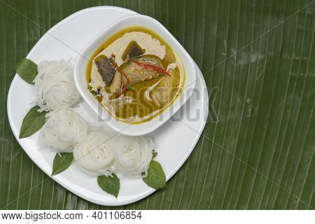 Top View Of Rice Vermicelli With Green Curry Chicken In White Plate And Bowl Place On Green Banana L