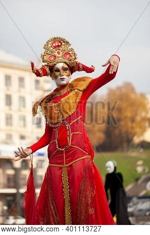 Man In A Red Carnival Costume On Stilts Against The Background Of The Cityscape. People On Stilts In