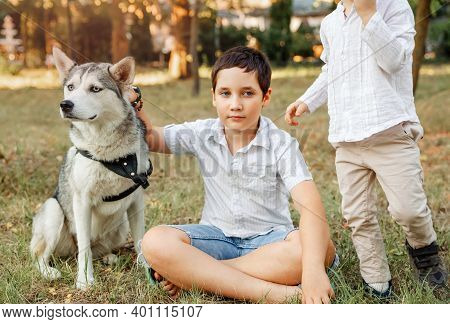 Children Playing With His Puppy In The Park. Young Cheerful Kids Resting At The Garden. Two Boys Sit