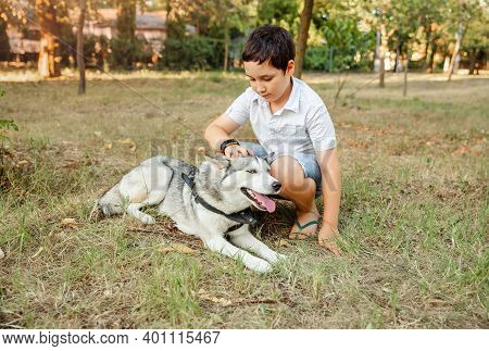 Handsome Young Boy Hugging His Puppy In Summer Park. Little Boy Playing With His Beautiful Dog Outdo