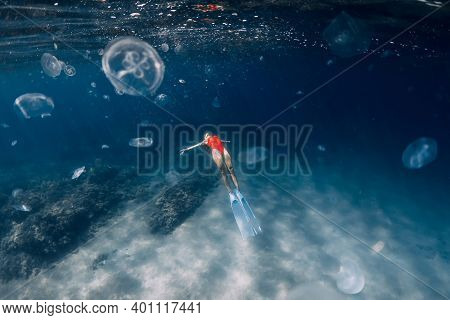 Woman Freediver With White Fins And Jellyfish Underwater. Freediving With Jellyfish In Blue Ocean