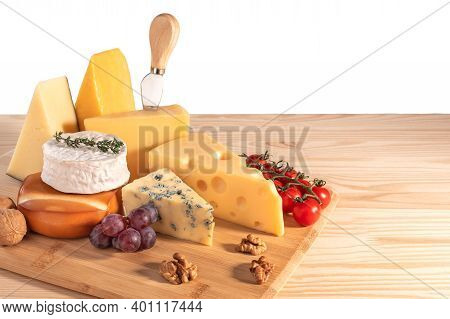 Assortment Of Different Types Of Cheese With Walnuts, Tomato And Grapes Isolated On White Background