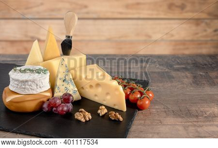 Different Types Cheese With Walnuts And Grapes On Rustic Wooden Background. Blue Cheese Dorblu, Smok