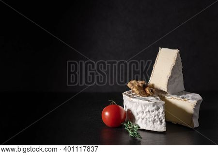 Brie Cheese With Tomato And Walnut On Black Background. Brie Type Of Cheese. Camembert. Fresh Brie C