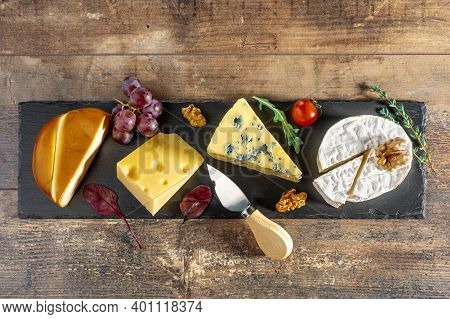 Cheese Plate. Different Cheeses Laid Out On Long Black Stone Board. Blue Cheese Dorblu, Smoked Sulug