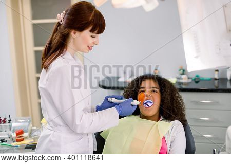 Female Dentist Performing Dental Filling Procedure To A Little Mixed Raced School Girl In Pediatric