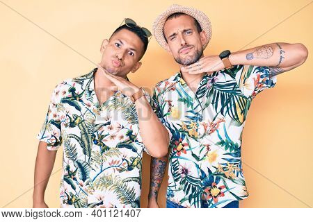 Young gay couple of two men wearing summer hat and hawaiian shirt cutting throat with hand as knife, threaten aggression with furious violence