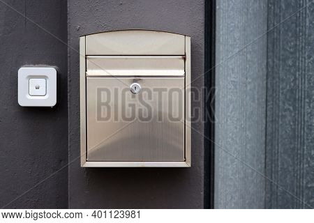 A Modern-style Metal Mailbox, Or Letterbox, Affixed To The Exterior Black And Gray Wall