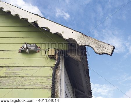 Side View Of Rusty Light Green Caribbean House With Rustic Roof And Electrical Installation Under Tr