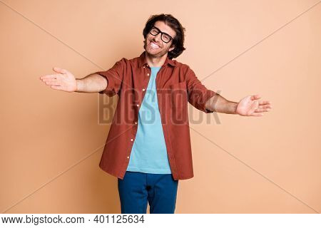 Photo Of Positive Guy Open Arms Want Hug You Toothy Smile Wear Eyewear Brown T-shirt Isolated Beige