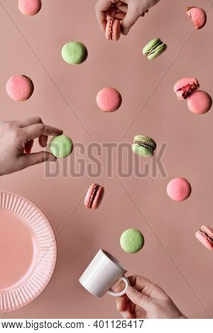 Levitation Of Macaroons, Creative Food Concept. Flying Macaroons, Plate, Several Hands With Half Mac