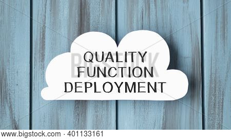 White Card In Cloud Shape With Text Quality Function Deployment On Stylish Wooden Background